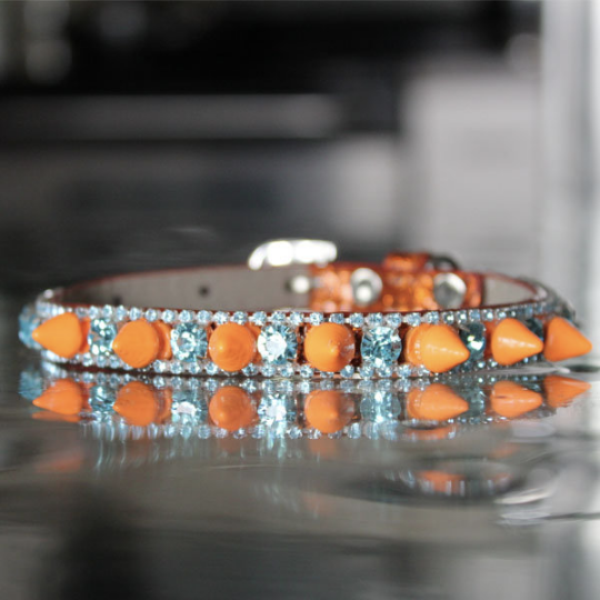 This Pop Rock Pet Collar was inspired by Ke$ha. It's a unique blend of colors that are crazy beautiful! It brings out your unconventional style, with a supernatural flair. It's perfect to wear when you are making any cat or dog cameo appearances. Made to propel your creativity as you flow to massive levels of success, this collar's style gives your audience a dose of potent stage power and inspiration. Set the stage with a warrior spirit of confidence, with all of the magic in the world to weave into many different looks before your fan's eyes. Being Orange Spike with Blue Topaz Rhinestone on an Orange Glitter Collar, it's a bold statement piece to take on to celebrate life and beauty.